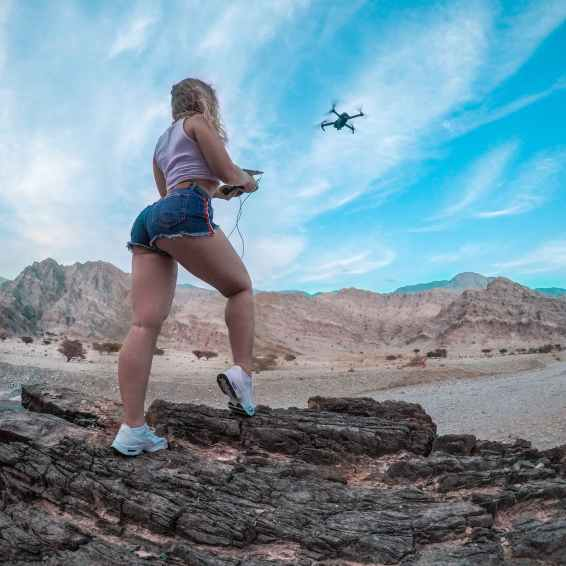 low angle shot of woman flying a drone